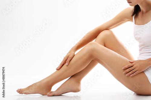 Fotografia  Cellulit. Kobieta sprawdza rozstępy na nogach