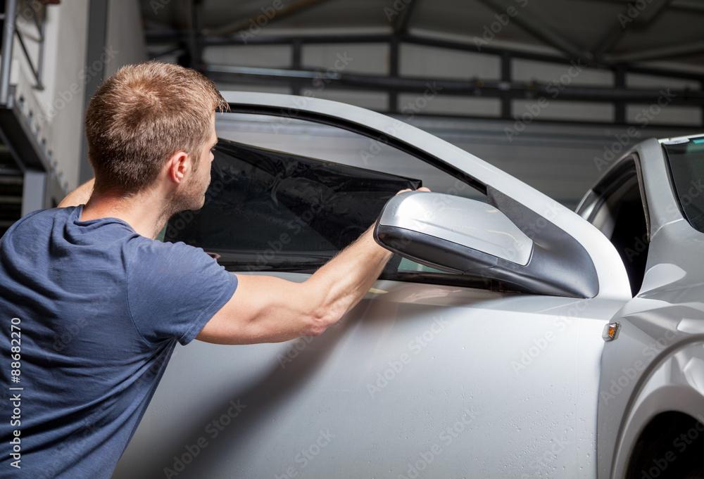 Fototapety, obrazy: Applying tinting foil on a car window