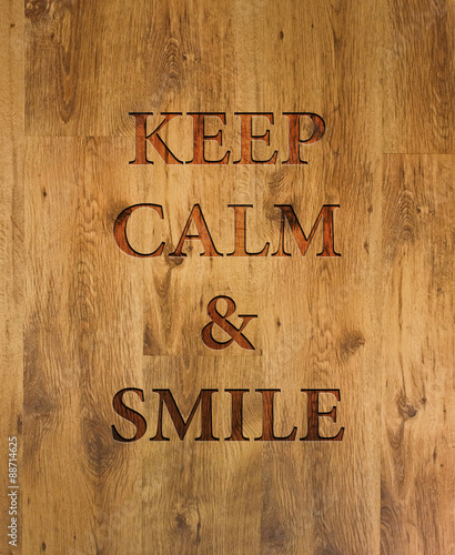 Text Keep Calm & Smile engraved in wooden background Canvas Print