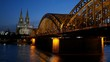 Gothic Cathedral and iron bridge across Rhine river after sunset. Cologne, Germany