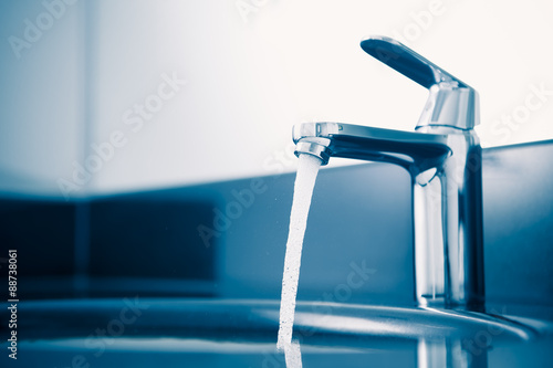Fotografia  faucet with flowing water, blue tone