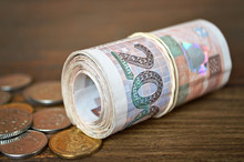 Coins And Rolled Banknotes Tied With Rubber Band
