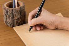 Hand Writing A Notebook On Table