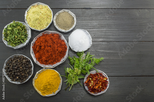 Different spices in shiny bowls on a dark wooden table Poster