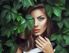 Exy Beauty Girl With Coral Lips. Provocative Green Make Up. Luxury Woman With Green Eyes. Fashion Brunette Portrait In Wild Leaves (grapes),  Natural Background. Gorgeous Woman Face. Long Hair