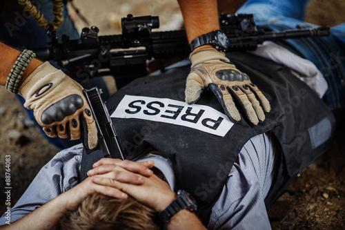 Photo  terrorists holding a gun to a journalist head
