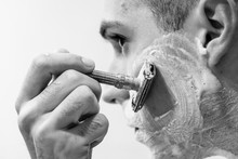 Handsome Young Man Is Shaving His Face With Razorblade And Looking At The Mirror