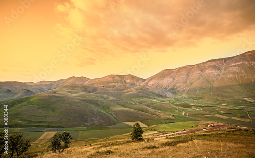 Foto auf Gartenposter Hugel warm sunset landscape. Mountains and fields background. italy