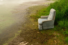 Old Recliner Sitting On Shore Of Swampy Lake