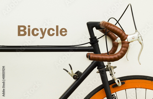 Some of old bicycle on white wall with word on space left side.