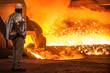 canvas print picture - Roheisenerzeugung: Arbeiter kontrolliert den Abstich am Hochofen
