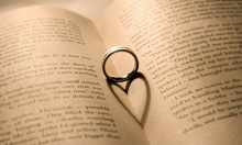 A Silver Ring Casts A Heart-shape Shadow On An Opened Book.