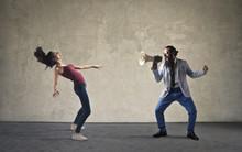 Man Screaming Into A Megaphone Towards A Woman