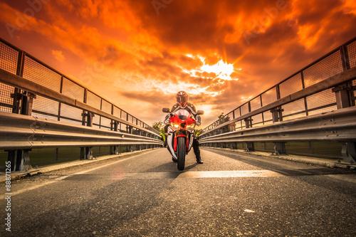 Fotografija  Moto da strada pronta alla partenza sotto un cielo rosso al tramonto