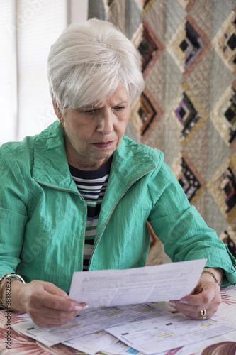 Fotografia, Obraz  A mature woman looking over medical bills