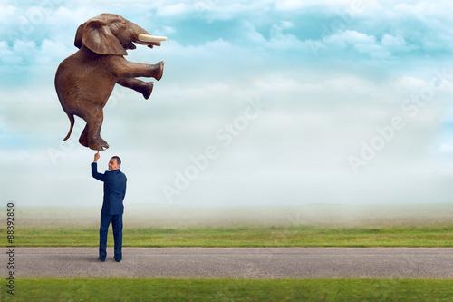 Fotografia  businessman holding an elephant with one finger