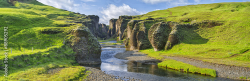 Photo Stands Canyon green hills of canyon with river and sky in Iceland