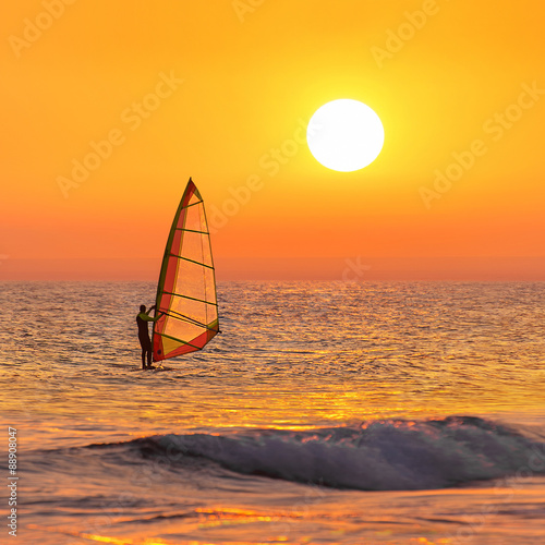 obraz lub plakat Windsurfer silhouette at sea sunset. Summertime watersports