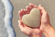 Hands Holding Sandy Heart At Beach Against Sea Waves