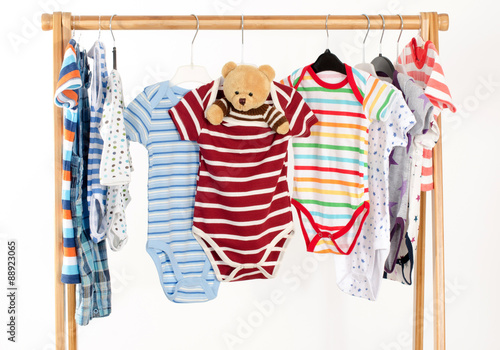9e404813d Dressing closet with clothes arranged on hangers.Colorful onesie of ...