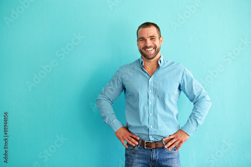 obraz dibond Happy man in front of turquoise wall