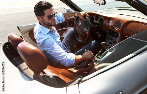 Fotografia  Handsome man near the car. Luxury life.