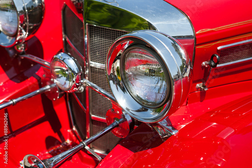 Red detail on the headlight of a vintage car Poster