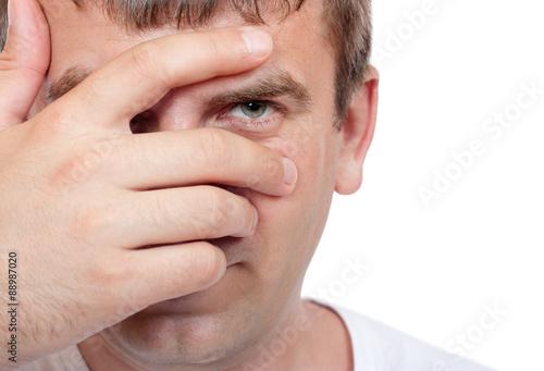 Fotografie, Obraz  Man peeking through fingers close-up on a white background