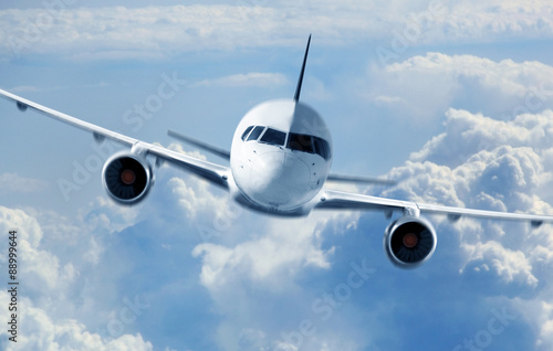plakat Passenger Airliner flying in the clouds