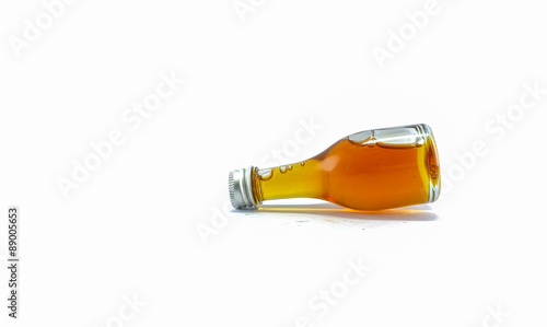Honey in a glass bottle isolated on white background