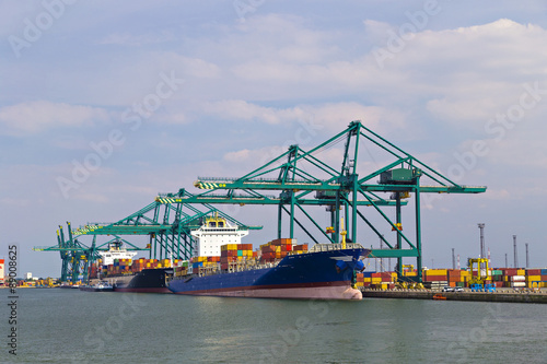Foto op Plexiglas Antwerpen Huge container ship loaded with cranes in Antwerp container terminal