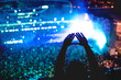 canvas print picture - Man showing love at concert, silhouette of hands making gestures with lights background