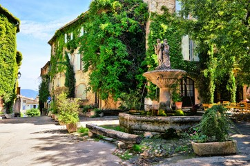 Fototapeta Leafy town square with fountain in a picturesque village in Provence, France