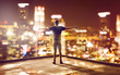 canvas print picture - Happy man faces skyline at night