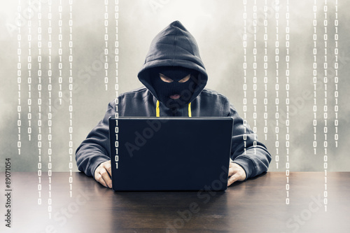 Fotografía  Masked computer hacker attacking internet services with binary code illustration