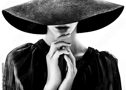 Beautiful woman with full lips in black hat poses on white Fototapet