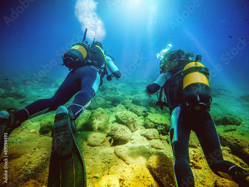 obraz lub plakat Two divers swimming away from camera. Blue water background.