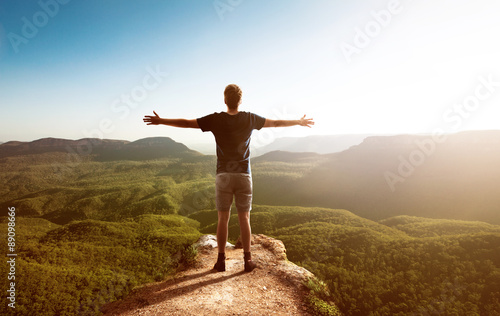 Happy man faces landscape with forest