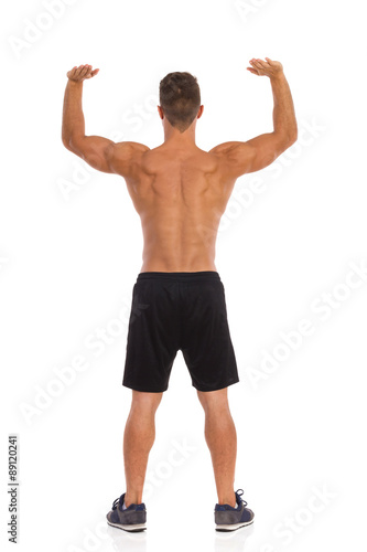 Muscular Man Holding Something Over His Head. Rear view. Full length studio shot isolated on white.