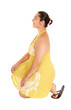 Pretty woman in yellow dress kneeling.