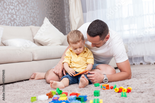 Fotografia, Obraz  Cheerful young man is playing with his kid