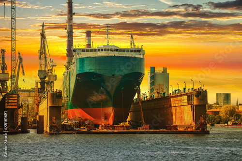 Ship being repaired in dry dock at sunset in Gdansk, Poland. Fototapeta