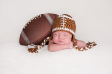 Newborn Baby Boy Wearing A Crocheted Football Hat