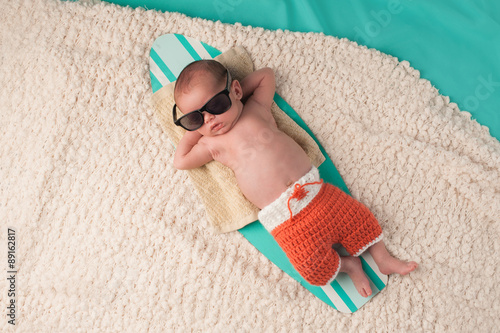 obraz PCV Newborn Baby Boy Sleeping on a Surfboard