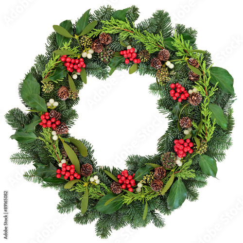 Photo  Traditional Christmas Wreath  with holly, ivy, mistletoe and winter greenery over white background
