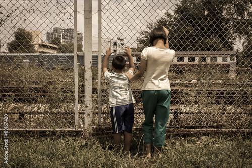 Fotografie, Obraz  asian girl and boy sad  hand hold jail at Railroad,railway stati