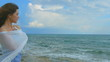 Horizontal panorama of beautiful lonely woman on sea shore, hair waving in wind