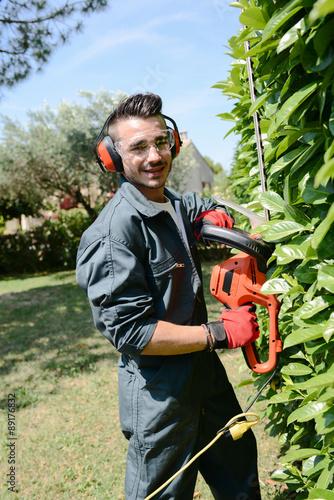 Photo sur Aluminium Noir handsome young man gardener trimming hedgerow in park outdoor