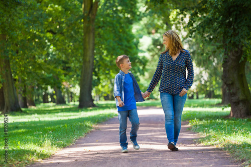 Photo  young woman with son walking through avenue