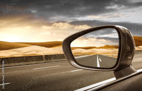 Fotografia strada nel deserto riflessa nello specchietto retrovisore esterno